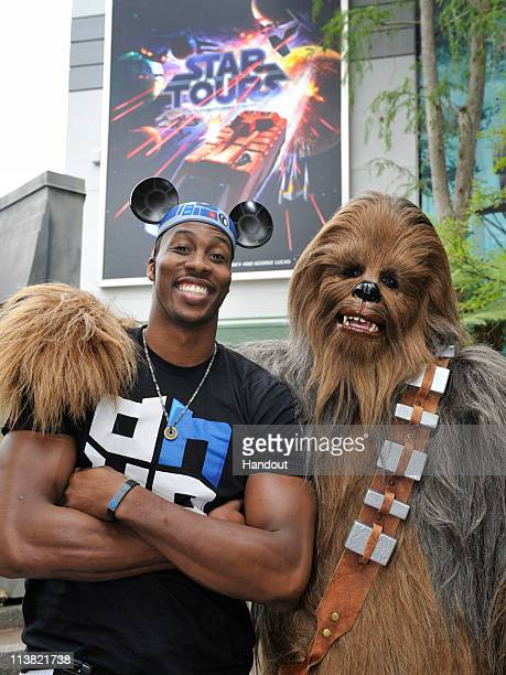 Orlando Magic center Dwight Howard poses with 'Star Wars' character Chewbacca in front of the new 'Star Tours The Adventures Continue' attraction...