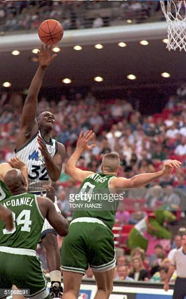 Orlando Magic center Shaquille O'Neal goes over the top of Boston Celtics forward Xavier McDaniel and center Eric Montross during the first period of...