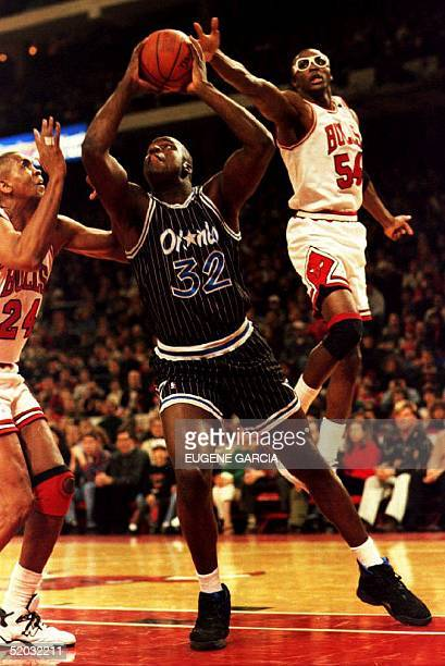 Orlando Magic center Shaquille O'Neal goes up for a shot as Chicago Bulls Horace Grant lunges to attempt a block in Chicago IL 25 December 1994 as...