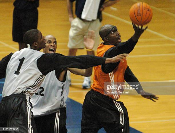 Orlando Magic forward Bo Outlaw right battles Trevor Ariza and Kasib Powell for a loose ball during the team's training camp in Jacksonville Florida...