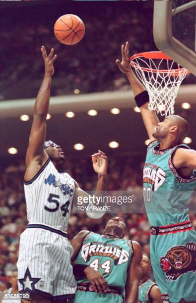 Orlando Magic forward Horace Grant goes over the top on Vancouver Grizzlies forward Kenny Gattison and center Benoit Benjamin for two points during...