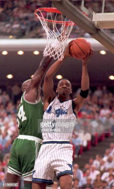 Orlando Magic guard Anfernee Hardaway draws a foul from Boston Celtics forward Xavier McDaniel as he slam dunks a basket during the first period of...