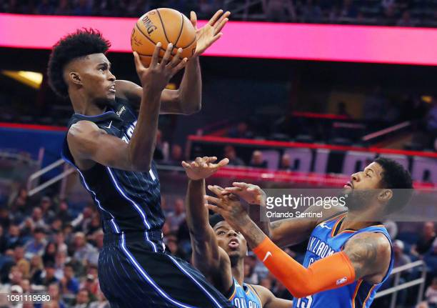 Orlando Magic guard Jonathan Isaac drives for a basket in front of Oklahoma City Thunder forward Paul George on Tuesday January 29 2019 at the Amway...