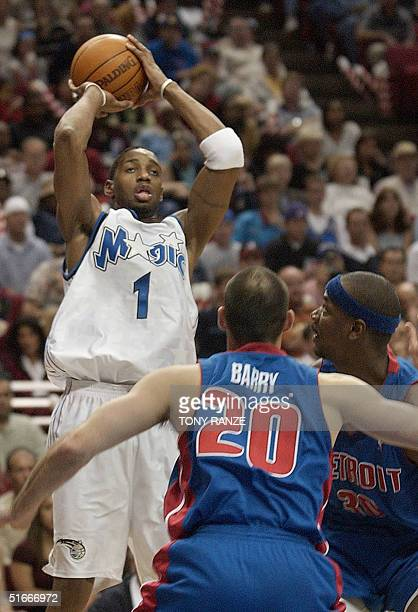 Orlando Magic guard Tracy McGrady scores over the top of Detroit Pistons' guard Jon Barry and Pistons' forward Clifford Robinson during the fourth...