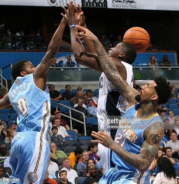 Orlando Magic guard Victor Oladipo middle loses the ball between Denver Nuggets guard Aaron Brooks and Denver forward Wilson Chandler at the Amway...