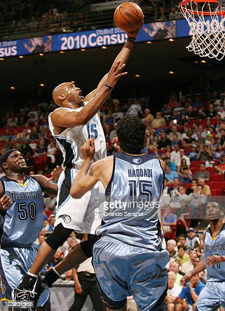 Orlando Magic guard Vince Carter scores over Memphis Grizzlies center Hamed Haddadi and forward Zach Randolph during an NBA game at Amway Arena in...