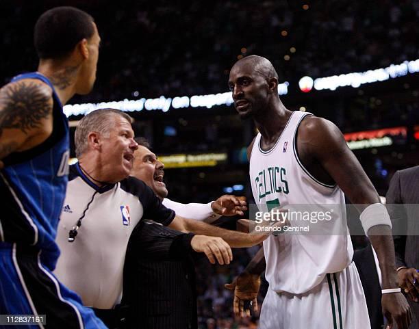Orlando Magic head coach Stan Van Gundy and referee Bob Delaney restrain Boston Celtics forward Kevin Garnett and Magic forward Matt Barnes during...