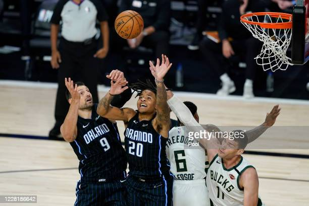 Orlando Magic's Nikola Vucevic and Markelle Fultz fight for a rebound with Milwaukee Bucks' Eric Bledsoe and Brook Lopez the second half of an NBA...