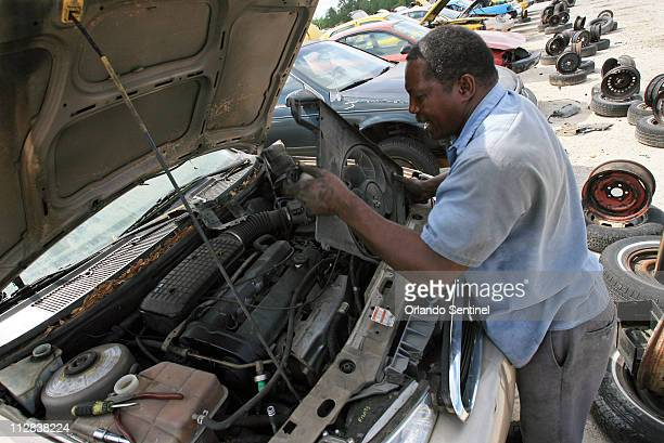 Orlando mechanic Adam Burnam pulls out the fan to get to the wiring harness of a 1998 Mercury Contour to repair a customer's vehicle at UPullPay on...