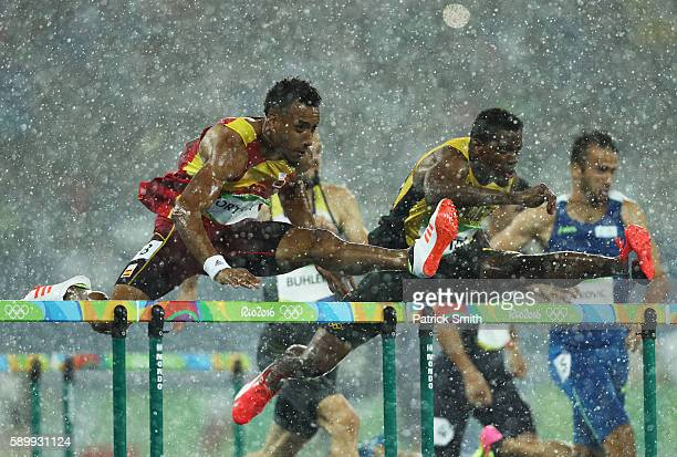 Orlando Ortega of Spain and Deuce Carter of Jamaica compete in the rain during the Men's 110m Hurdles Round 1 Heat 2 on Day 10 of the Rio 2016...