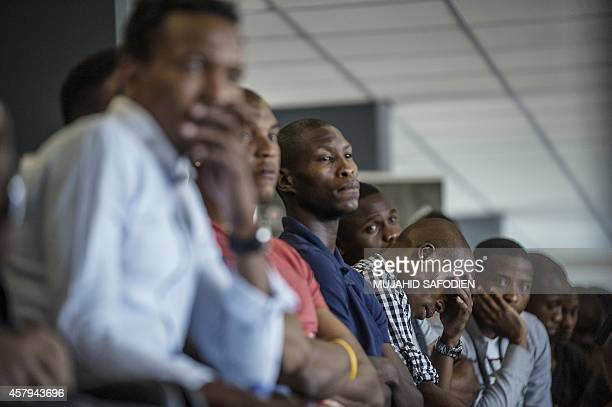 Orlando Pirate players stand at the Midrand Stadium on October 27 2014 in Johannesburg after their team goalkeeper Senzo Meyiwa was shot dead South...