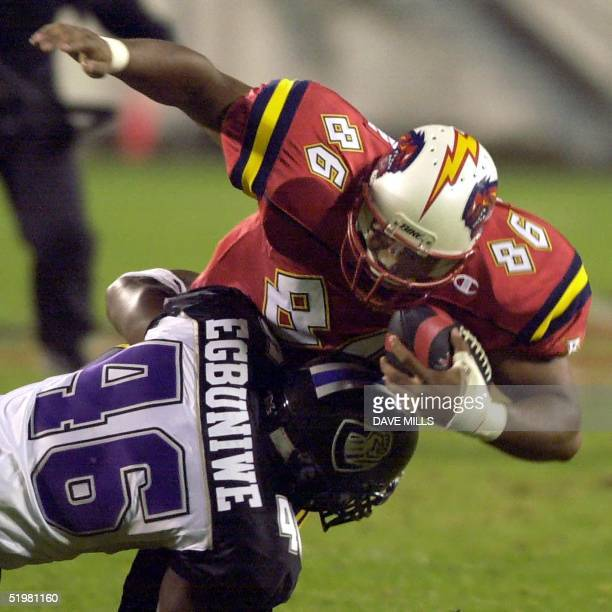 Orlando Rage tight end Terrance Huston is tackled by Chicago Enforcers linebacker Chike Egbuniwe during the first half of the new XFL league opening...