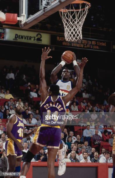 Orlando Woolridge, Small Forward for the Denver Nuggets drives to the hoop as Sam Perkins of the Los Angeles Lakers attempts to block during their...