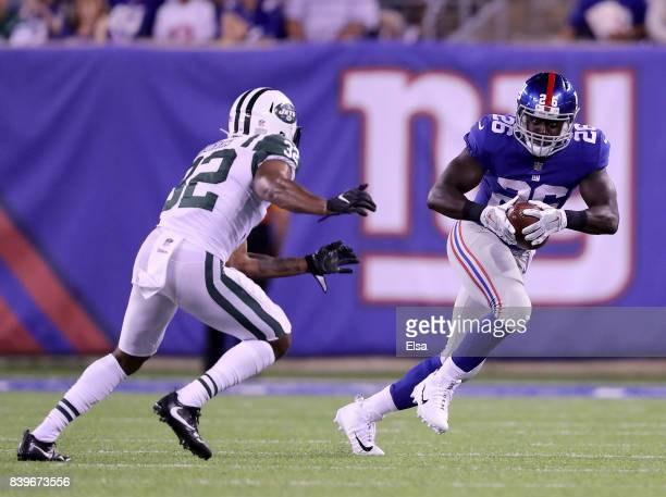 Orleans Darkwa of the New York Giants carries the ball as Juston Burris of the New York Jets defends during a preseason game on August 26 2017 at...