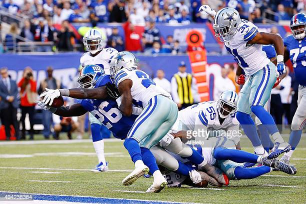 Orleans Darkwa of the New York Giants dives across the goal-line for a second quarter touchdown under pressure from Morris Claiborne of the Dallas...