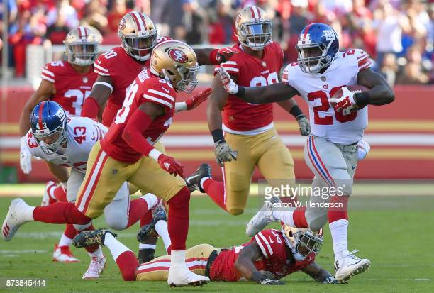 Orleans Darkwa of the New York Giants running with the ball fights off the tackle of Adrian Colbert of the San Francisco 49ers during their NFL...