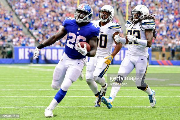 Orleans Darkwa of the New York Giants runs the ball past Charmeachealle Moore and Tre Boston of the Los Angeles Chargers for a first quarter...