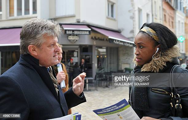 French farright Front National party regional president Philippe Loiseau is pictured as he talks with a supporter as he distributes leaflets for his...