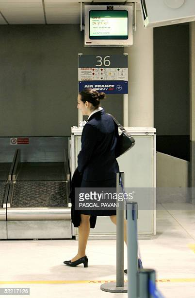 An air hostess walks under a screen announcing the strike as passengers are left stranded in Orly West air terminal south of Paris 19 February 2005...