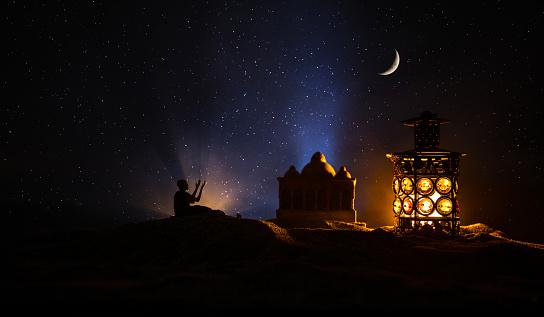 Ornamental Arabic lantern with burning candle glowing at night. Festive greeting card, invitation for Muslim holy month Ramadan Kareem. 1141090214