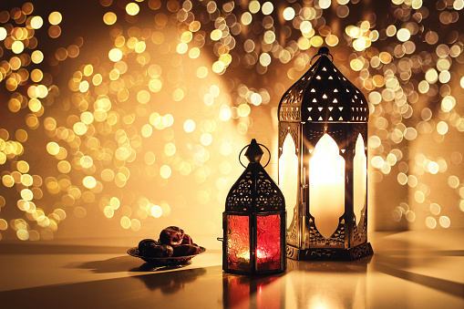 Ornamental Arabic lanterns with burning candles. Glittering golden bokeh lights. Plate with date fruit on the table. Greeting card for Muslim holiday Ramadan Kareem. Iftar dinner background. 1134972492