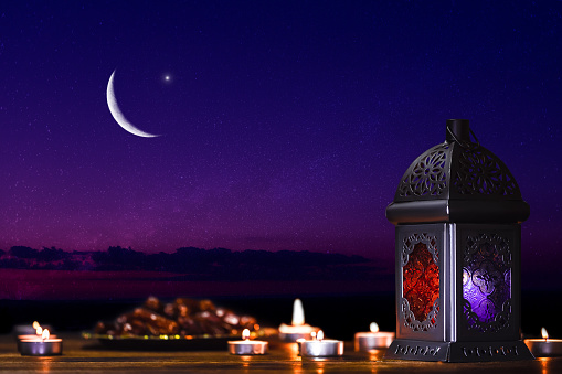 Ornamental dark Moroccan, Arabic lantern and dates on on an old wooden table with the night sky and the Crescent moon and the stars behind. Greeting card for Muslim community holy month Ramadan Kareem 1147301148
