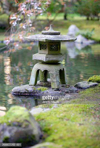 ornamental stone pagoda in garden pond - jeremy chan stock pictures, royalty-free photos & images