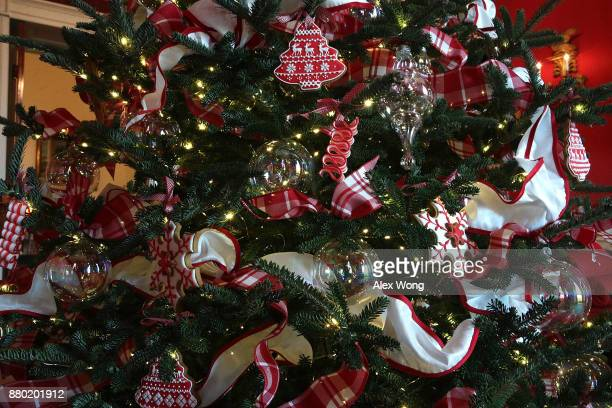 Ornaments are hung on a Christmas tree in the Red Room at the White House during a press preview of the 2017 holiday decorations November 27 2017 in...
