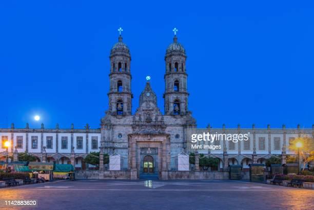 ornate church overlooking town square at dusk, zapapan, jalisco, mexico - zapopan fotografías e imágenes de stock