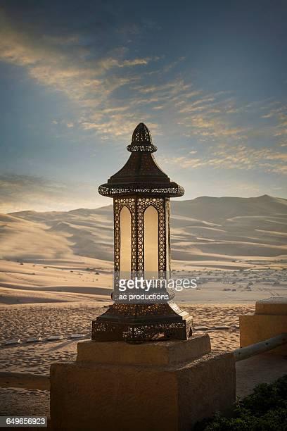 Ornate lantern on wall in desert