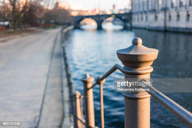 Ornate railing of the Spree riverbank at dusk.
