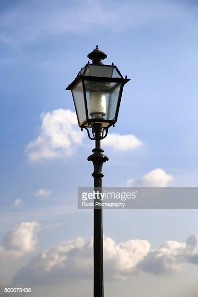 Ornate street lantern on the river banks of the Arno River, in Florence, Italy