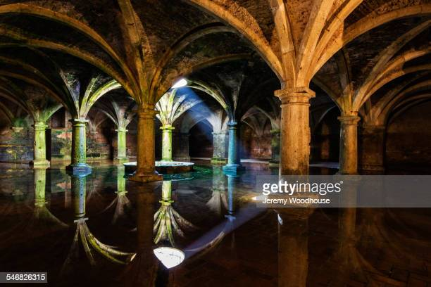 Ornate tile arches illuminated near skylight reflecting in water