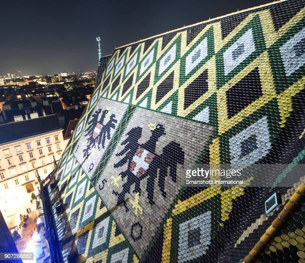 Ornate Vienna Cathedral rooftop with characteristic colored tiles and designs illuminated at night, Austria