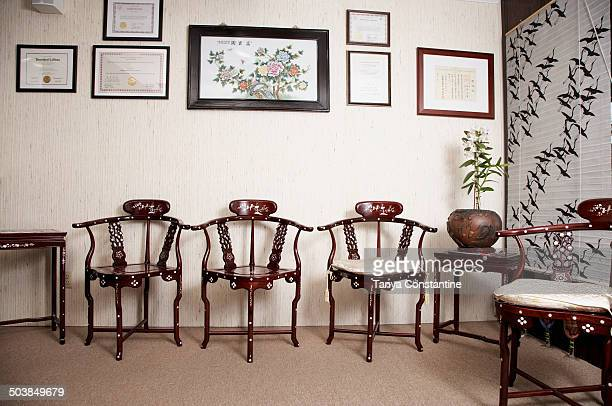 Ornate wooden chairs and picture frames in living room