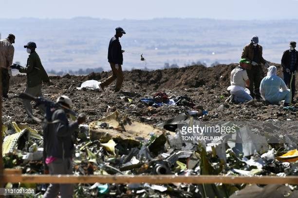 Oromo men hired to assist forensic investigators are at work at the crash site of an Ethiopian airways operated Boeing 737 MAX aircraft on March 16...