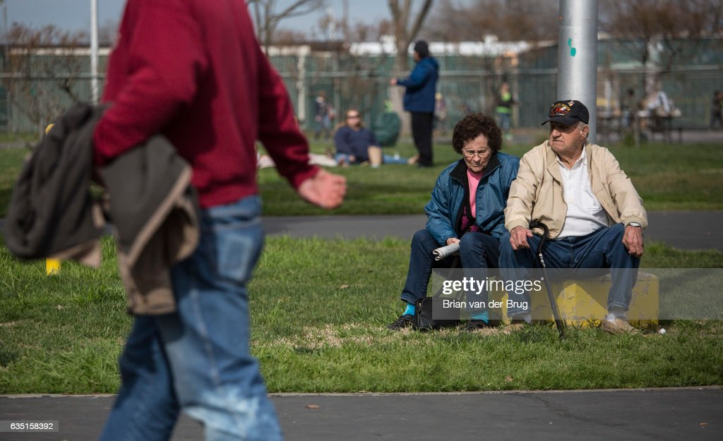 Oroville evacuees Bill O'Kelley, 86, and his wife Doris O'Kelley, 84, sit near a flagpole on the grounds of the Silver Dollar Fair evacuation shelter in Chico, Calif., on Feb. 13, 2017. The pair want to go home.