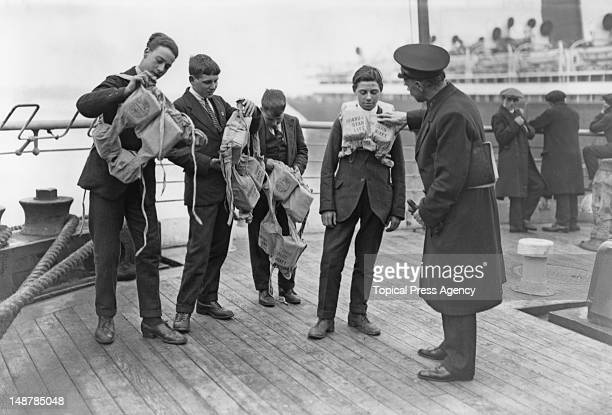 Orphaned boys from the Dr Barnardo's Homes leave for a new life in Canada on the 'RMS Antonia' UK April 1923 Here they try on life jackets under the...