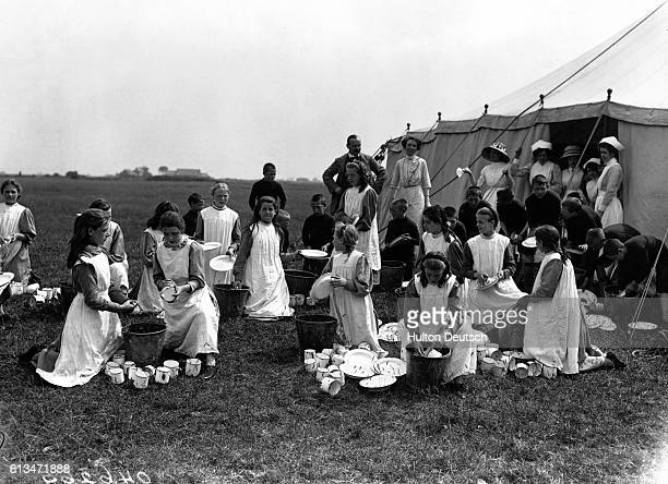 Orphaned children from the Islington workhouse wash cups and plates outside their tent in a field on Canvey Island July 1912