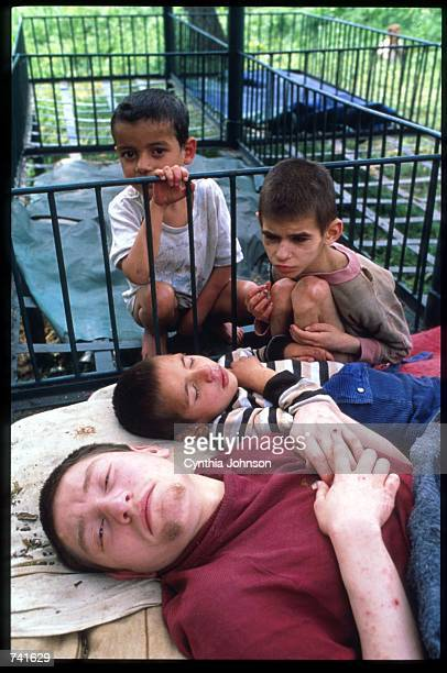 Orphaned children sit outside May 15 1990 in Romania Nicolae Ceausescu required women to bear at least five children causing the placement of 150000...