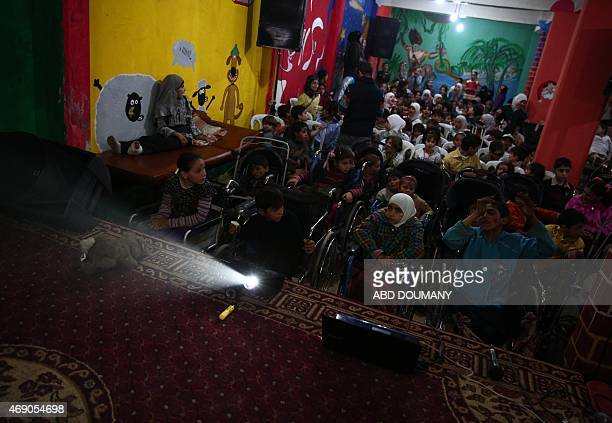 Orphaned injured and disabled Syrian children watch cartoons as they attend a party organized by a nongovernmental organisation Douma Society and the...