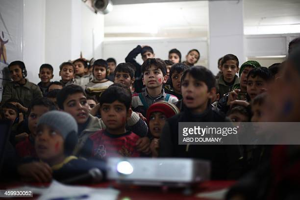 Orphaned Syrian children who lost their parents in the three and a half year conflict ravaging their country watch a video at a school for orphans...