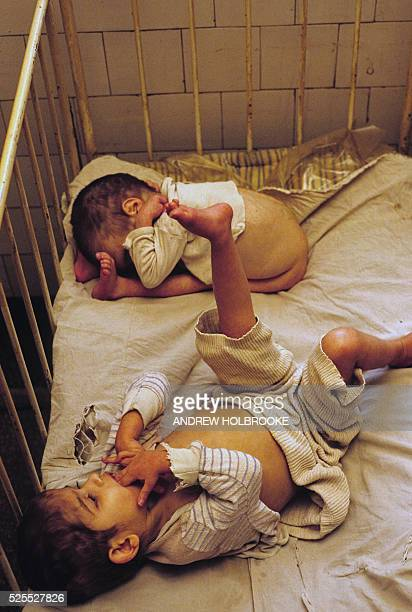 Orphans at the Riul Vadului Mental Asylum sharing a crib | Location Altania Romania