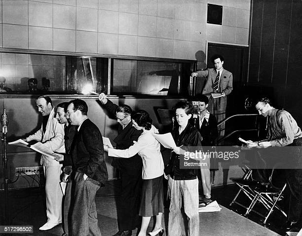 Orson Welles guiding genius of the Mercury Theatre of the Air is shown {hands upraised} in action here at a microphone as he directed a rehearsal of...