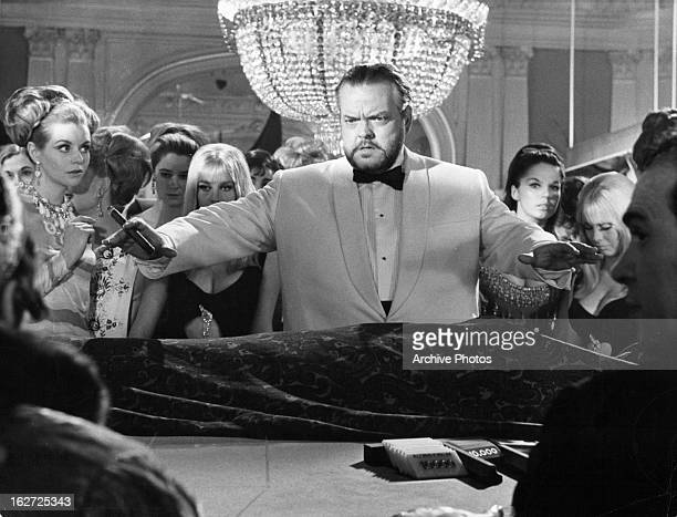 Orson Welles raising arms at the baccarat table in a scene from the film 'Casino Royale' 1967