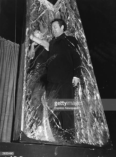 Orson Welles the American director and actor with a lady in what appears to be a cocoon of cellophane Original Publication People Disc HM0036