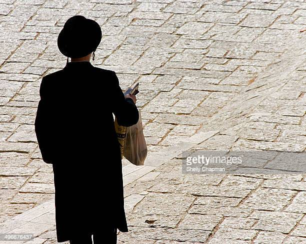 CONTENT] Orthdox Jew wearing dark clothing and a hat in the streets of Jerusalem on a sunny day