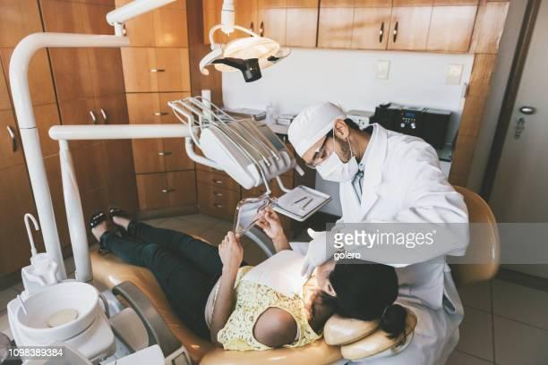 ortodontista medicando jovem mulher nos dentes na clínica odontológica - dentista - fotografias e filmes do acervo