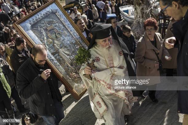 Orthodox believers carry a picture of the Lord during the annual Epiphany Day and the blessing of the waters celebrations in Piraeus near Athens...