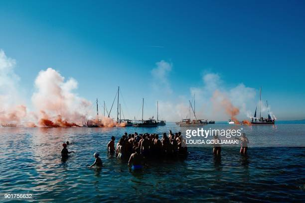 TOPSHOT Orthodox believers gather around a wooden cross thrown into the water by a priest off a beach of Athens' coastal suburb on January 6 during...